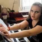 Ali citește partituri de pian în Braille.